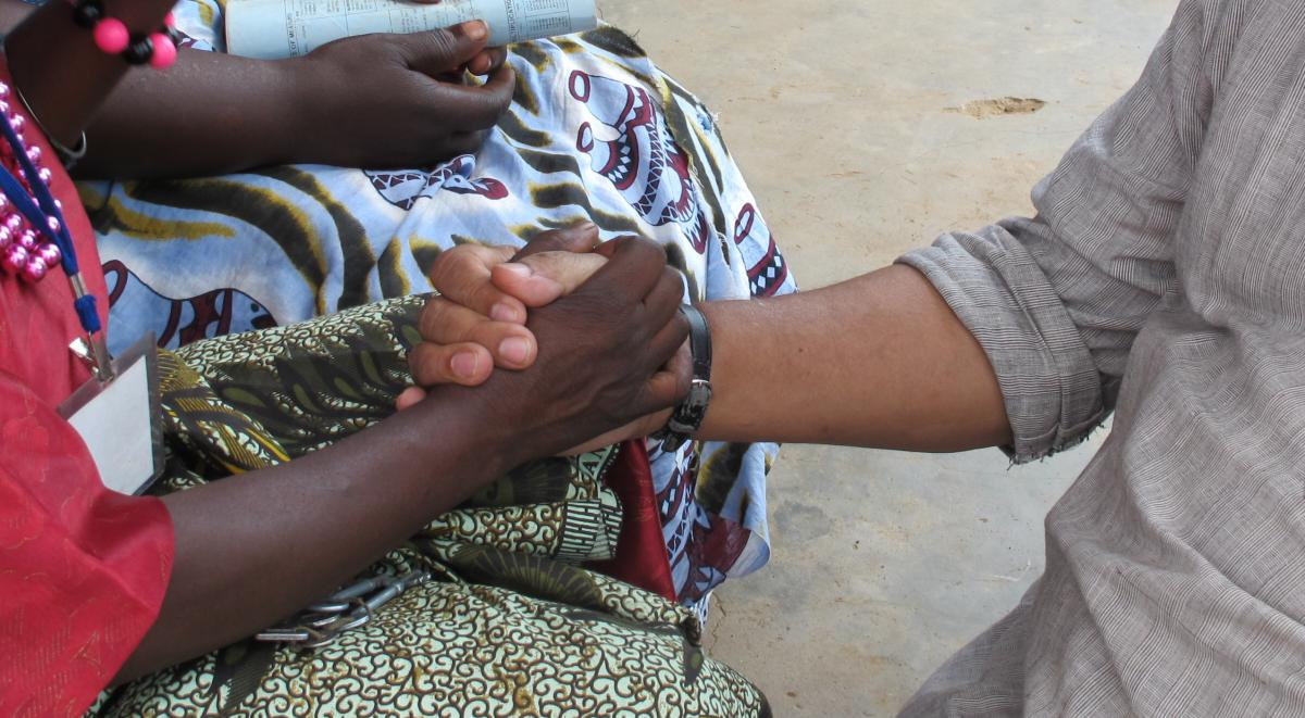 Bunker Roy of Barefoot College holds the hand of a rural woman in Africa