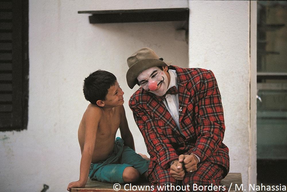 Clown making young boy in Croatia laugh
