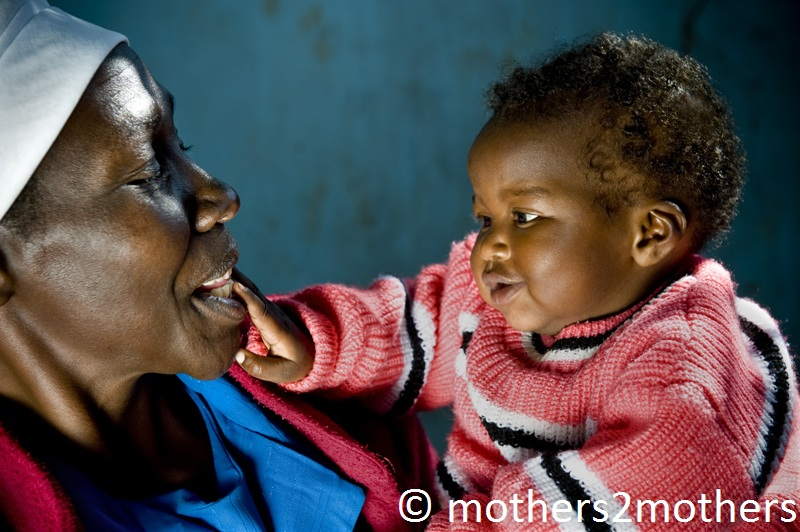 Mother holds her smiling baby