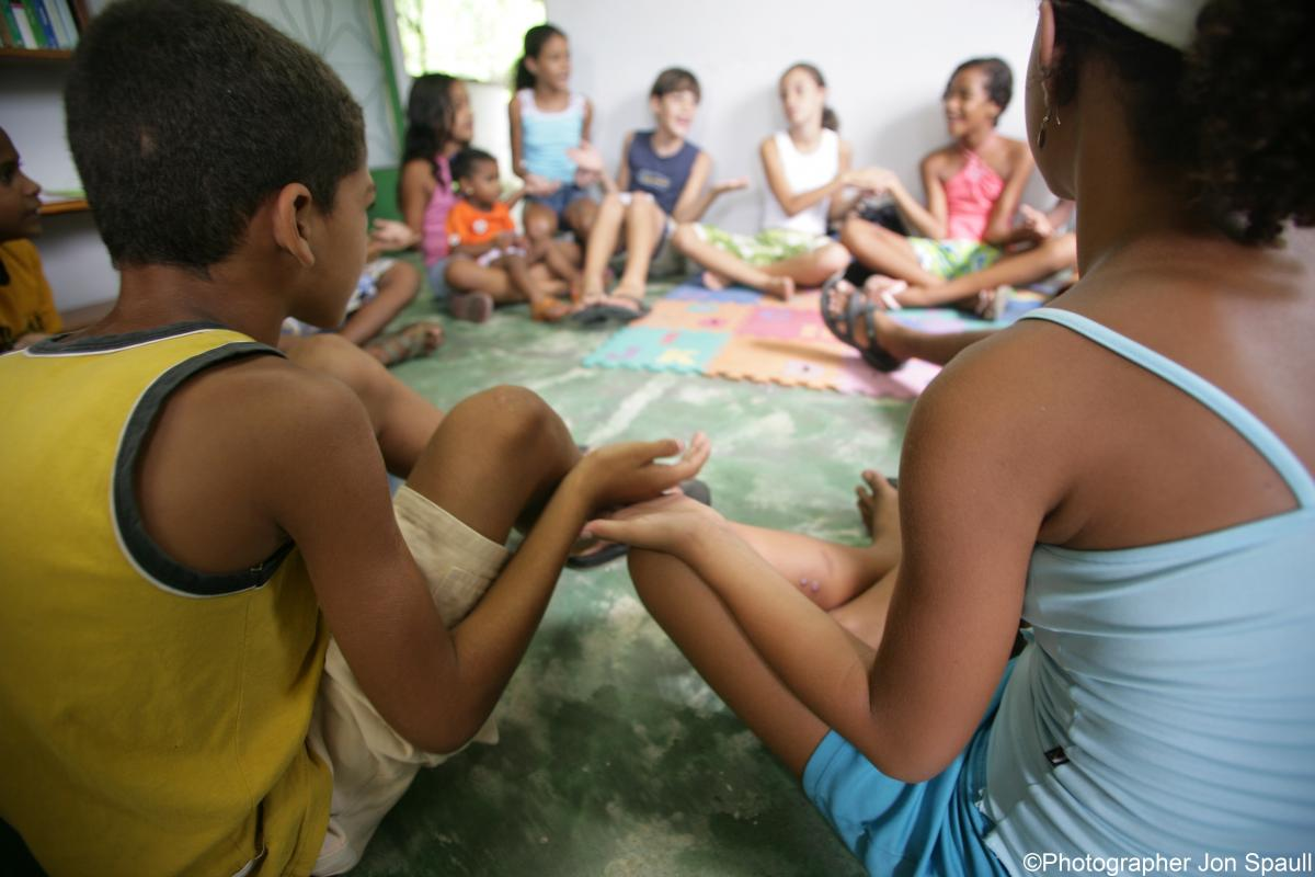 Children sit in circle holding hands at a Promundo meeting