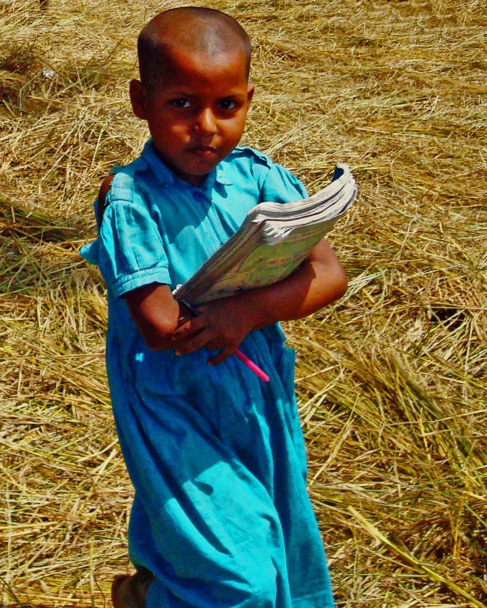 Schoolgirl in Bangladesh carrying her books