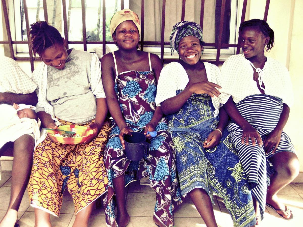 Four pregnant women sit outside the Aberdeen Women's Centre smiling