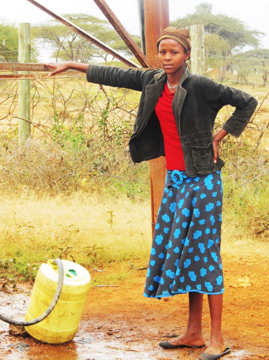 Young Maasai woman fetches water