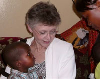 Francoise Barre-Sinoussi with an African boy and his mother