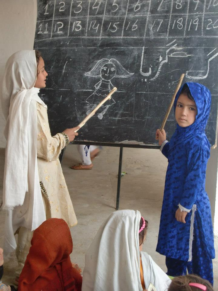 Rural girls learn in front of a blackboard in Pakistan