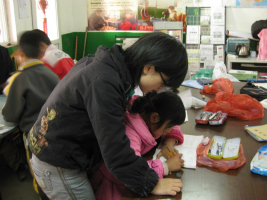 A tutor helps a young migrant child in China